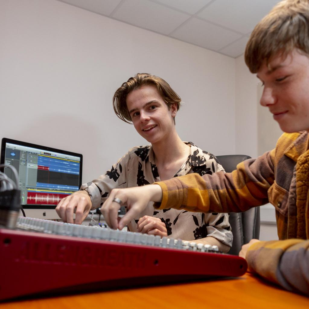 Two students turning dials in music studio on mixing desk