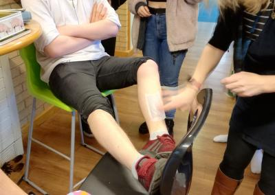 Student getting leg waxed for charity