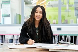 Student sat smiling in art studio
