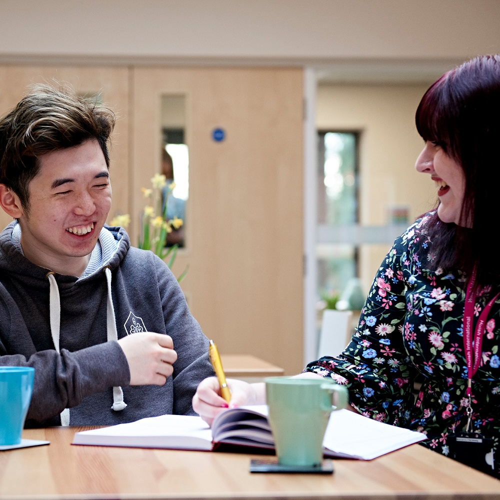 Student laughing with staff member over tea