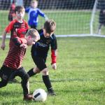 Young Huish Tiger player kicking ball mid match