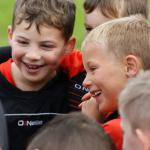 Young Huish Tigers footballers smiling in huddle