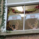 Window with paper reindeers peeking out