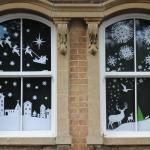 Winter town and woodland scene made of cut out paper in a window