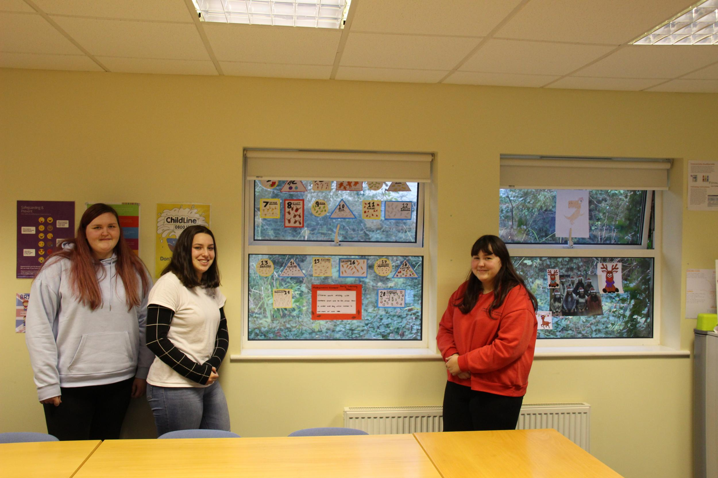 Childcare and education students with their window displays