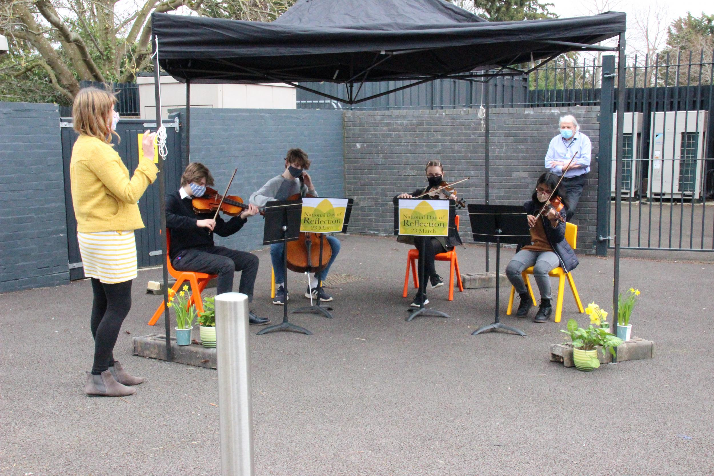 Course Manager Kathryn Foyle and student string quartet sat outside under canopy