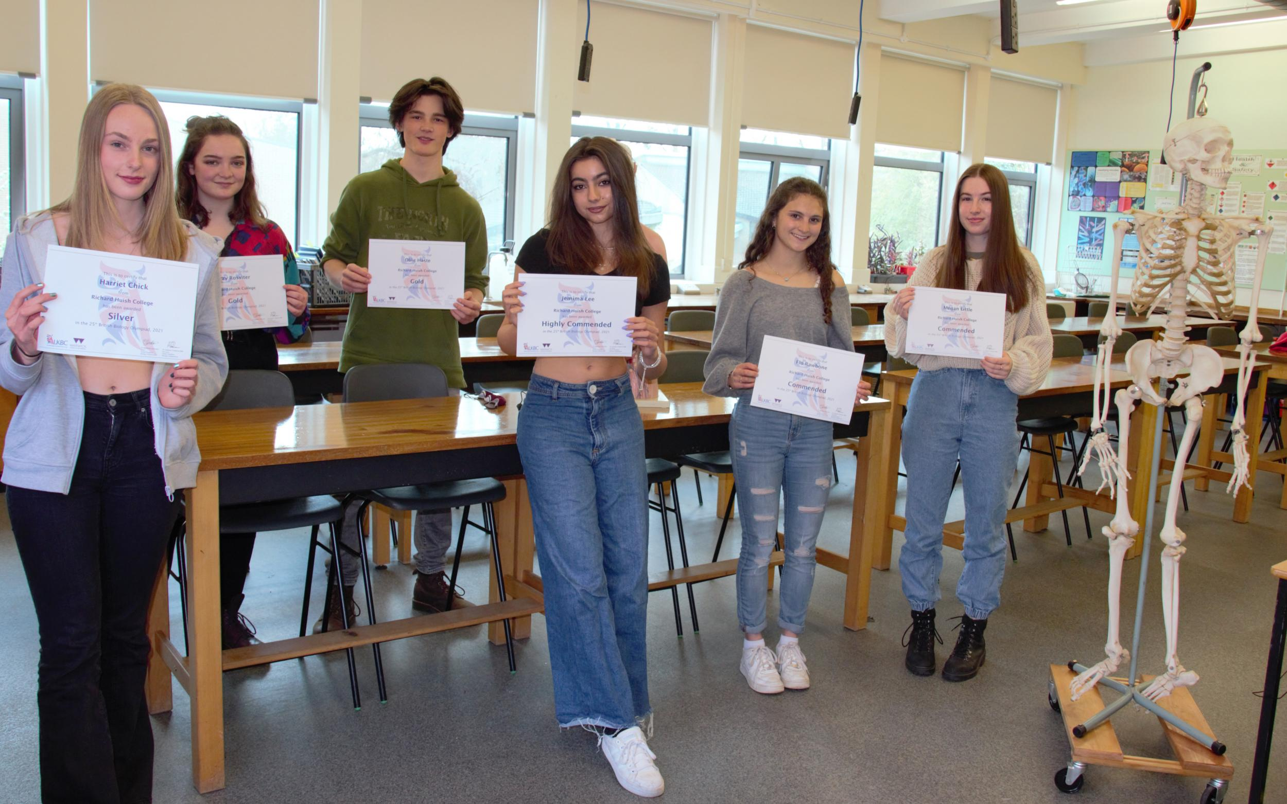 students holding certificates in biology lab
