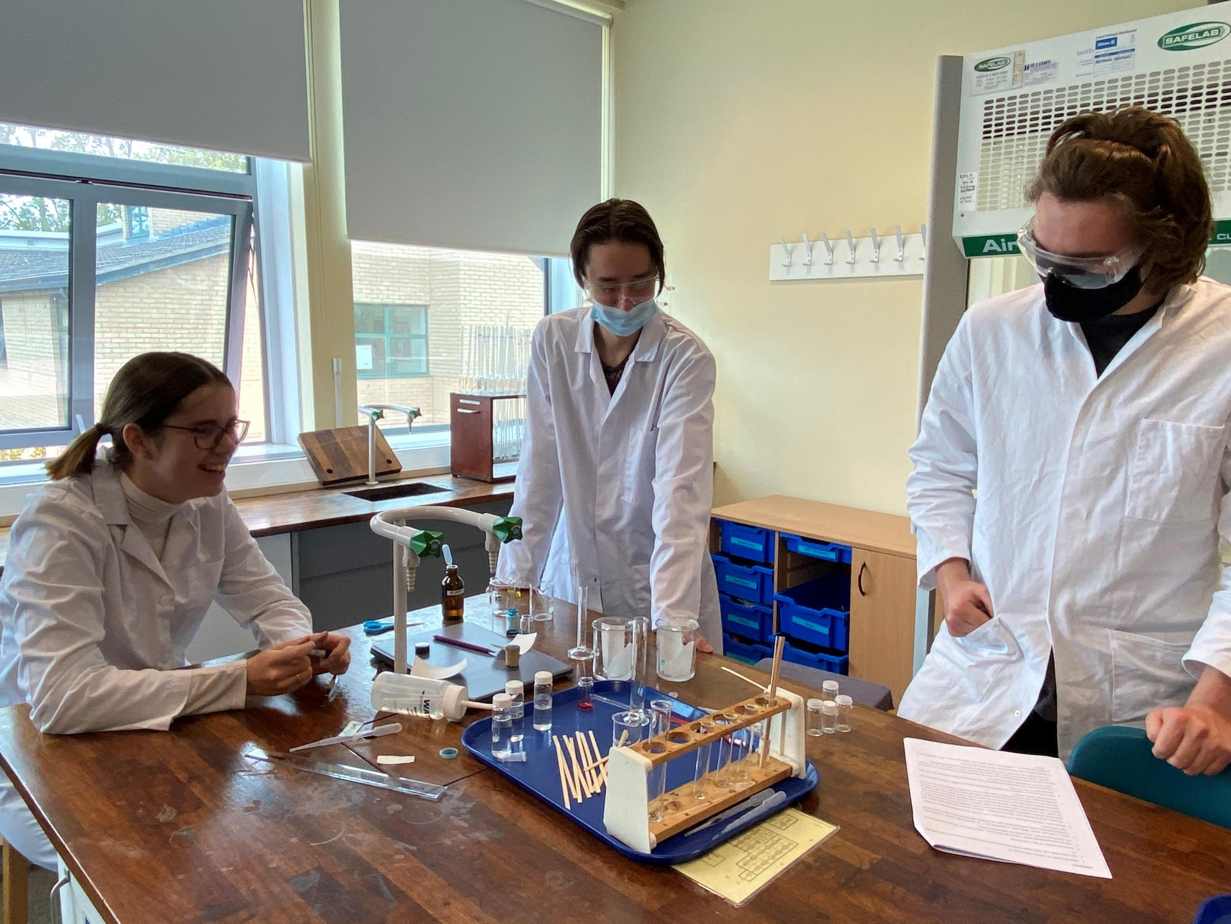 Three chemistry students in lab doing an experiement