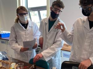 Three students doing an experiment in the lab
