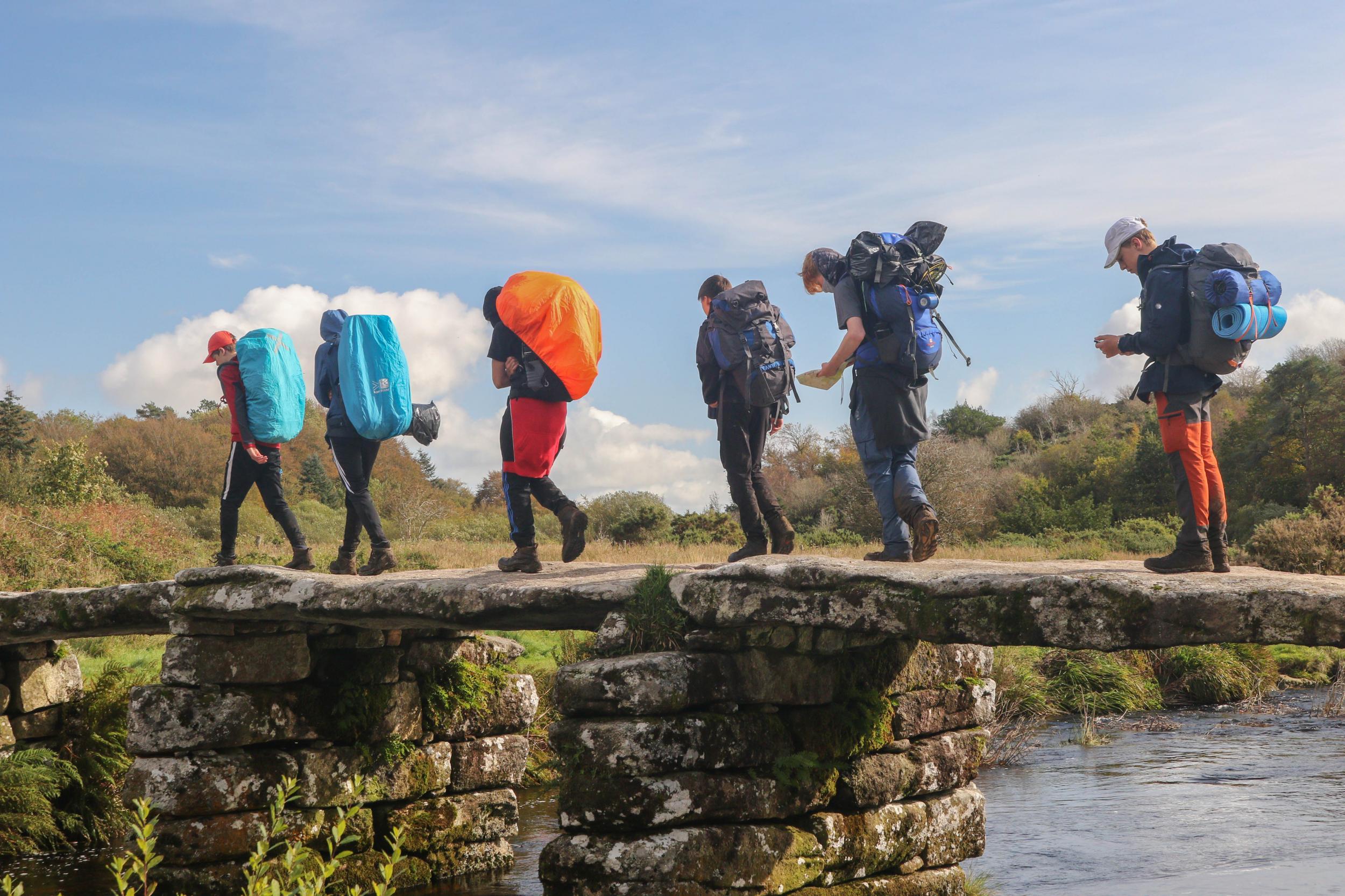 students with large rucksacks walking over stone bridge