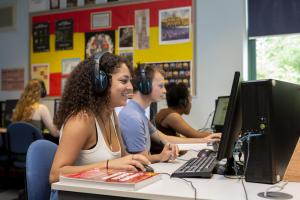 Students in the language lab with headphones on looking at computers with spanish flag behind them