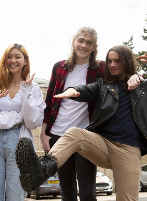 Group of friends stood close together, one is kicking in the air and another is posing doing a peace sign