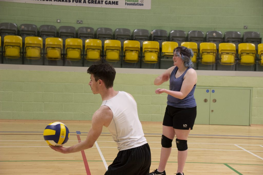Two students playing volleyball